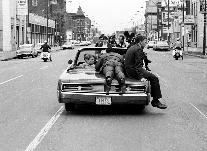 Jimmy Breslin, lying on trunk of car, interviewing, Robert F. Kennedy. (Image by Jim Hubbard.)