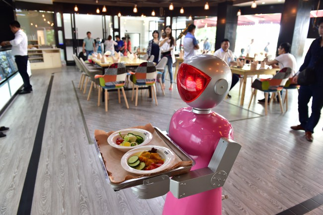 "YIWU, CHINA - MAY 18: (CHINA OUT) A ""female"" robot waiter delivers meals for customers at robot-themed restaurant on May 18, 2015 in Yiwu, Zhejiang province of China. Sophomore Xu Jinjin in 22 years old from Hospitality Management of Yiwu Industrial and Commercial College managed a restaurant where a pair of robot acted as waiters. The ""male"" one was named ""Little Blue"" (for in blue color) and the ""female"" one was ""Little Peach"" (for in pink) and they could help order meals and then delivered them to customers along the magnetic track and said: ""Here're your meals, please enjoy"". According to Xu Jinjin, They had contacted with the designer to present more robot waiters to make the restaurant a real one that depends completely on robots. (Photo by ChinaFotoPress via Getty Images)"